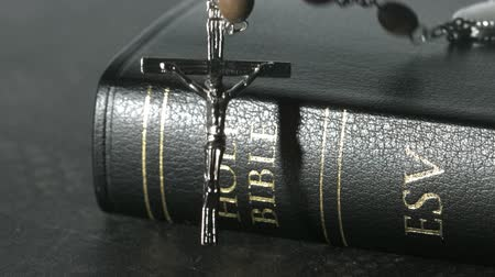 jehovah witness : Rosary beads falling onto a bible in slow motion