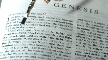 jehovah witness : Rosary beads falling onto the book of genesis in slow motion Stock Footage