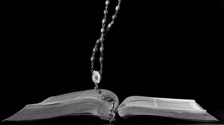 jehovah witness : Rosary beads falling onto open bible in slow motion Stock Footage