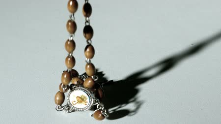 jehovah witness : Rosary beads casting a shadow and then falling on white surface in slow motion