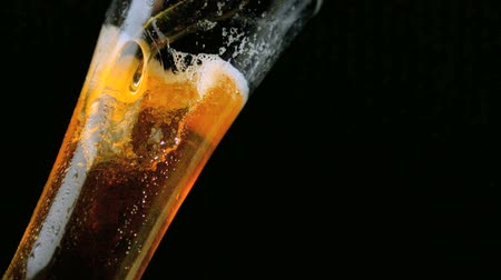 Beer pouring into glass on black background in slow motion