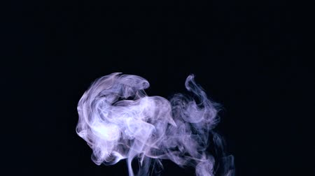 fumo : Rising puff of smoke on black background in slow motion