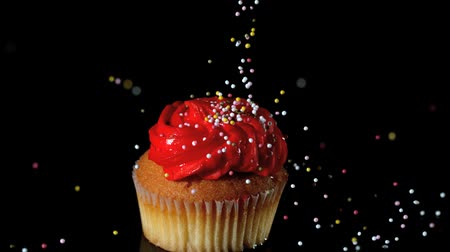 queque : Sprinkles falling onto red iced cupcake in slow motion