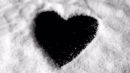 heart shaped : Heart shaped out in sugar blowing away in slow motion Stock Footage
