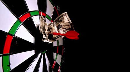 dart : Red dart with a dollar note hitting board in slow motion
