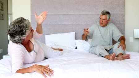 гнев : Mature couple having a dispute in the bed
