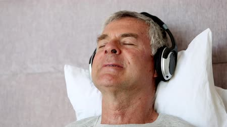 poduszka : Man moving his head while listening to music in his bed Wideo