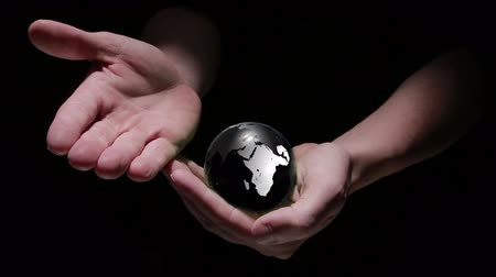 parlayan : Animation of hands revealing globe earth on black background