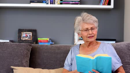 gülümseyen : Elderly woman reading book sitting on the couch in living room Stok Video