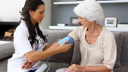 médicos : Home nurse checking her elderly patients blood pressure sitting on the couch