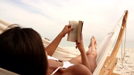 гамак : Woman relaxing on her hammock on the beach while reading a book Стоковые видеозаписи