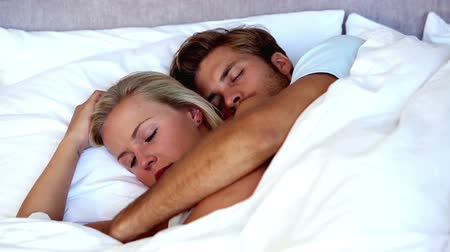 napping : Couple spooning in bed and sleeping peacefully