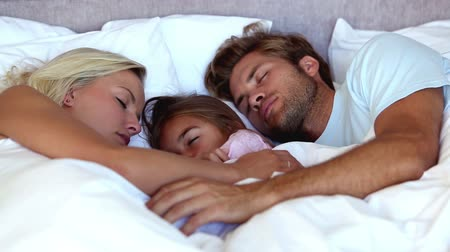 napping : Parents sleeping with their daughter all tucked up in bed
