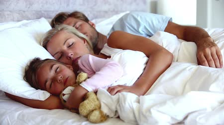 quarto doméstico : Parents and daughter holding teddy bear sleeping peacefully in bed together