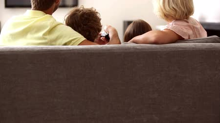 assistindo : Rear view of family watching tv at home on the couch