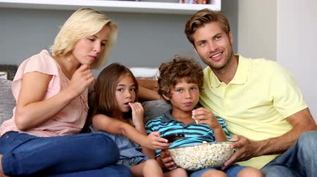 assistindo : Family eating popcorn and watching tv together on sofa at home