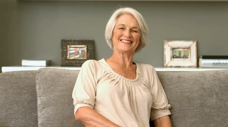 emekli : Happy retired woman smiling on couch in slow motion