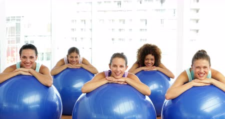 ćwiczenia : Fitness class in studio leaning on exercise balls smiling at camera at the gym