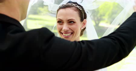 подвенечное платье : Groom lifting veil off beaming brides face on their wedding day
