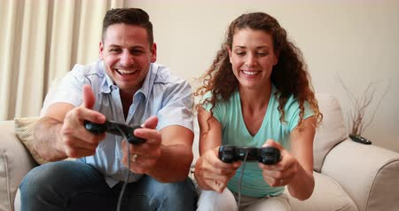 сидеть : Happy young couple sitting on sofa playing video games at home in the living room
