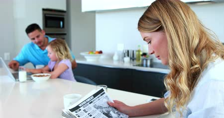 kitchen paper : Mother reading the paper while family has breakfast at home in the kitchen