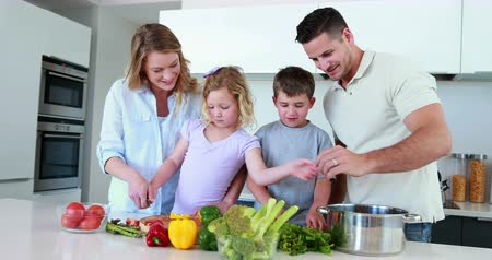 vacsora : Smiling family preparing a healthy dinner together at home in the kitchen