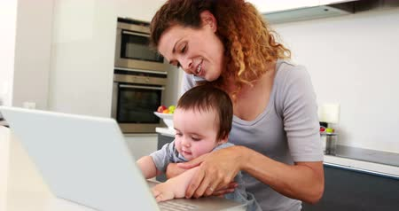 yapıştırma : Mother sitting with baby boy on lap using laptop and talking on phone at home in the kitchen