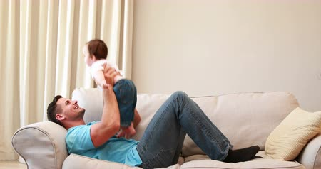 guy home : Father playing with his baby boy on the couch at home in the kitchen Stock Footage