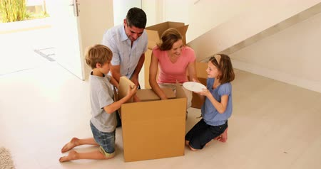 Домашняя жизнь : Happy family opening box in their new home in their new home Стоковые видеозаписи
