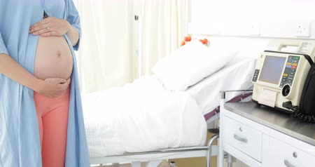 maternity hospital : Pregnant woman standing in hospital gown at the hospital Stock Footage
