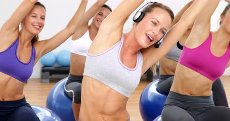 motivasyonel : Fitness class sitting on exercise balls stretching at the gym