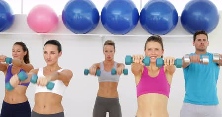 aeróbica : Aerobics class lifting dumbbells together at the gym