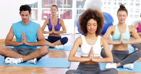 sınıf : Yoga class sitting in lotus pose together at the gym