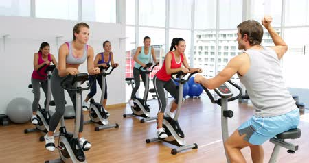 motivasyonel : Spinning class in fitness studio led by energetic instructor at the gym
