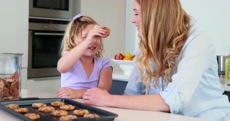keksz : Little girl having milk and cookies with her mother at home in the kitchen Stock mozgókép