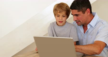 otec : Little boy using laptop with his father at the table at home in living room