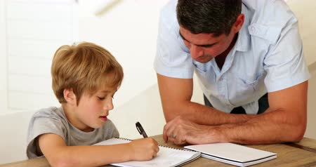 домашнее задание : Father helping his son with his homework at home in living room Стоковые видеозаписи