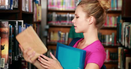 studenti : Allievo grazioso individuando un libro in biblioteca all'università