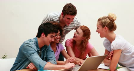 aluno : Cheerful students using laptop together at the university