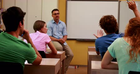 lesson : Lecturer sitting and speaking to his students in classroom at the university Stock Footage