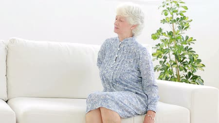 painéis : Old woman complaining of back pain in the living room