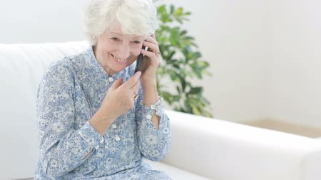 on the phone : Old woman calling with mobile phone on the couch Stock Footage