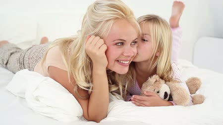 mother love : Girl kissing her mother in bed Stock Footage