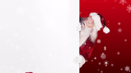 hediyeler : Digital animation of Santa peeking around gift card on festive background Stok Video