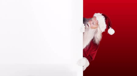 santa : Digital animation of Santa peeking around gift card on festive background Stock Footage