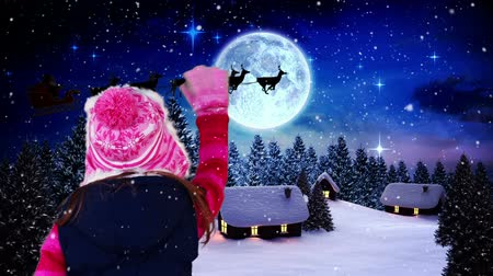 santa : Digital composite of Little girl waving to santa flying over village