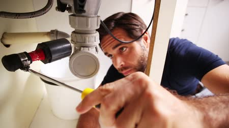 раковина : Handsome plumber using screwdriver to fix sink and smiling to camera Стоковые видеозаписи