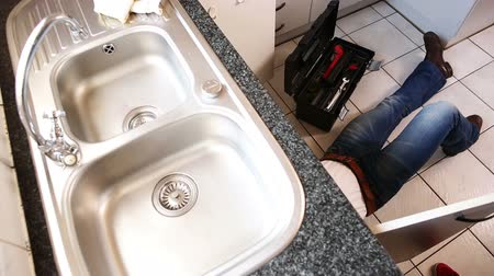 раковина : Plumber fixing the sink in a kitchen lying on the floor