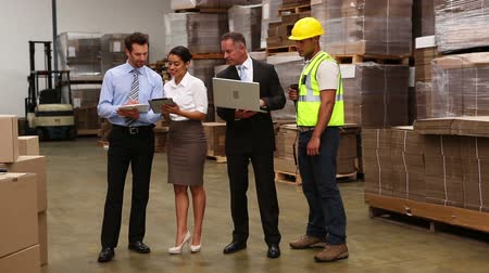 dialog : Warehouse managers and worker talking in a large warehouse