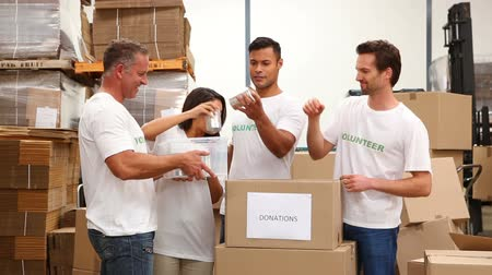 dobrovolník : Warehouse workers packing up donation boxes in a large warehouse